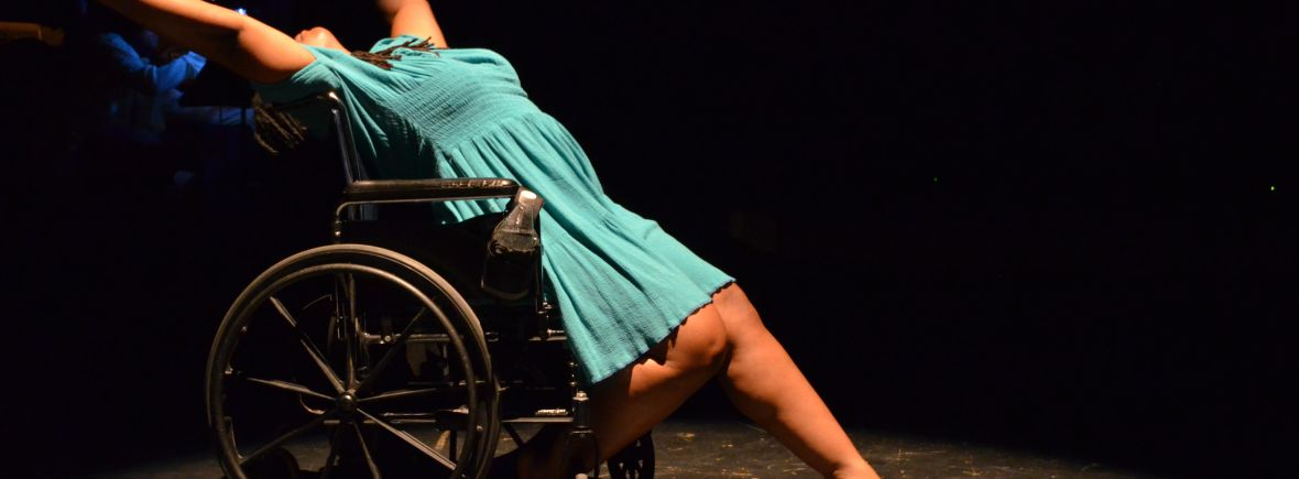 India Harville, African-American disabled dancer using a wheelchair is leaning back on her chair with her arms reaching behind her. She is wearing a teal dress and new shoes. Her head is not visible and is behind her arms.